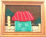 Artisan wall hanging with green house